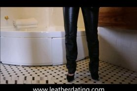 Sexy brunette in leather pants taking a shower