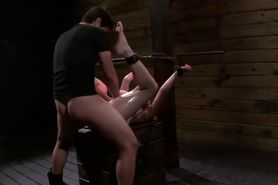 Chained busty redhead with legs in the air gets fucked
